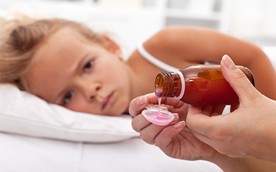 A sad young girl laying on a bed in the background of someone pouring medicine onto a spoon