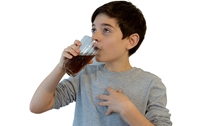 A young boy drinking a soft drink