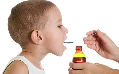 Child receiving a dose of cough syrup