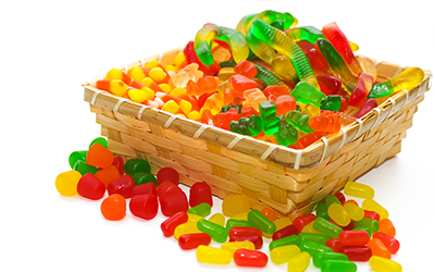 A basket of candies such as gummy worms, candy corn and gummy bears