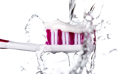 Toothbrush with toothpaste on it running under water